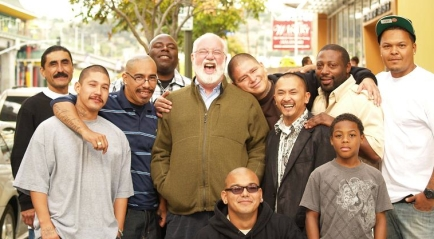 Father Gregory Boyle stands surrounded by former gang members who have become his friends, employees.